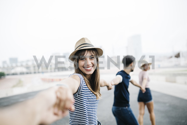 Spain, Barcelona, portrait of smiling young woman holding hands with her friends - JRFF000134