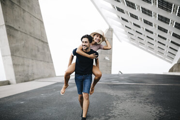 Spain, Barcelona, young man giving his girlfriend a piggyback ride - JRFF000140