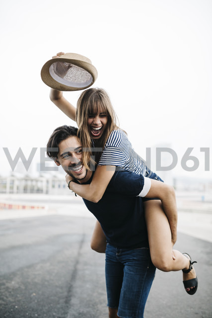 Spain, Barcelona, young man giving his girlfriend a piggyback ride - JRFF000143