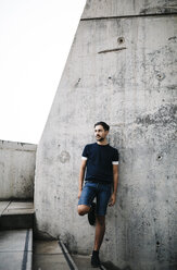 Spain, Barcelona, young man leaning against concrete wall - JRFF000149
