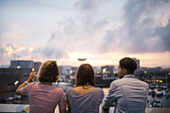 Spain, Barcelona, back view of three friends looking at view from a bridge - JRFF000152
