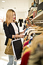 Young woman in fashion boutique shopping for clothes - JASF000197