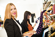 Young women in fashion boutique shopping for clothes - JASF000200