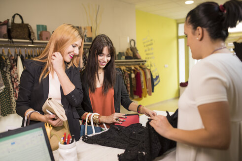 Young women in fashion boutique shopping for clothes - JASF000212