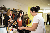 Young women in fashion boutique shopping for clothes - JASF000224