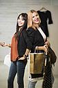 Young women in fashion boutique carrying shopping bags - JASF000230