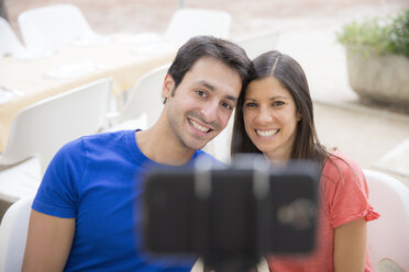 Happy couple using selfie stick for taking a selfie with smartphone - ERLF000064