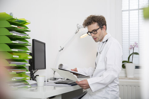 Doctor sitting at desk looking at document - FKF001442