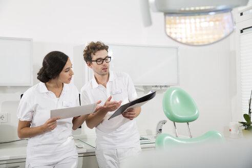 Two dentists in dental surgery preparing treatment - FKF001454