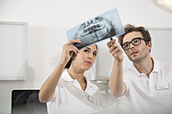 Two dentists in dental surgery discussing x-ray image - FKF001457