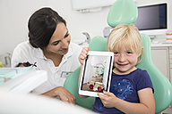 Dentist and smiling girl showing digital tablet in dentist's chair - FKF001475