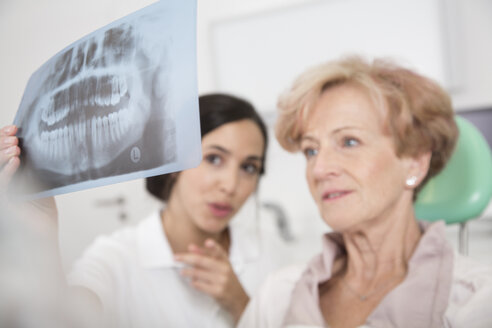 Dentist explaining x-ray image to senior woman in dentist's chair - FKF001478