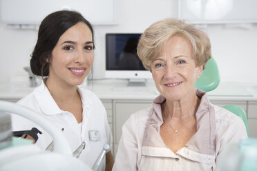 Dentist and smiling senior woman in dentist's chair - FKF001481
