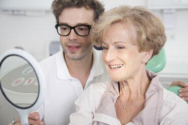 Senior woman in dentist's chair checking her teeth in mirror - FKF001484