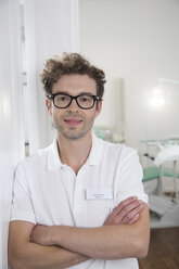 Portrait of smiling dentist at surgery - FKF001496