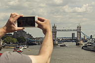 UK, London, man taking photo of Tower Bridge with his smartphone - ZMF000435