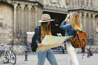 Spain, Barcelona, two young women on square with camera and map - EBS000943