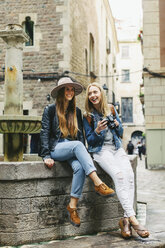 Spain, Barcelona, two happy young women at a fountain - EBSF000946