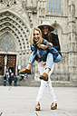 Spain, Barcelona, happy young woman carrying friend piggyback in the city - EBSF000955
