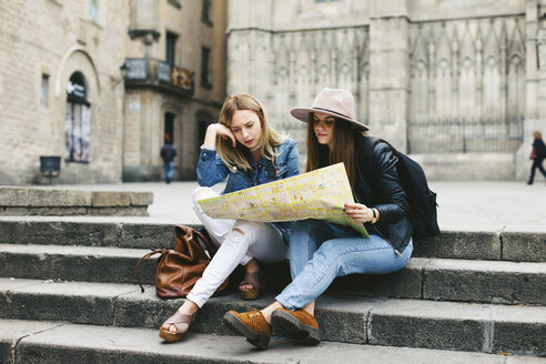 Spain, Barcelona, two young women reading map on stairs - EBS000958