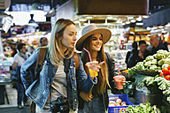 Two young women drinking smoothies on a market - EBS000967
