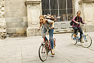 Spain, Barcelona, two happy young women riding bicycle in the city - EBSF000970