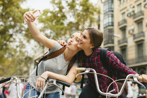 Spain, Barcelona, two young women on bicycles taking a selfie - EBSF000973