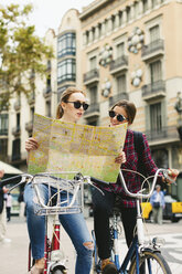 Spain, Barcelona, two young women with map on bicycles in the city - EBS000976
