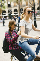 Spain, Barcelona, two happy young women sharing bicycle in the city - EBSF000979