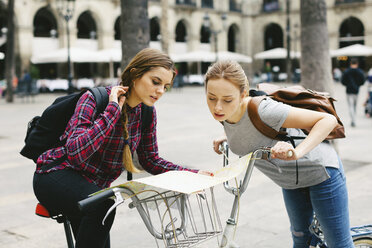 Spain, Barcelona, two young women with map on bicycles in the city - EBSF000982