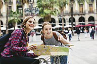 Spain, Barcelona, two young women with map on bicycles in the city - EBSF000985