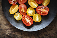 Halfed yellow and red cherry tomatoes on plate - EVGF002472