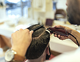 Barber cutting hair of a customer - MGOF000890