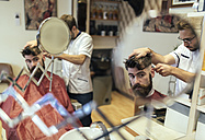 Reflection of barber cutting hair of a customer - MGOF000896