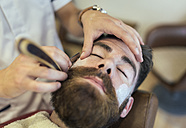 Barber shaving beard of a customer - MGOF000917