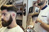 Customer checking his hairstyle in a barber shop - MGOF000920