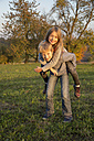 Portrait of boy giving his sister a piggy back ride on a meadow - SARF002235