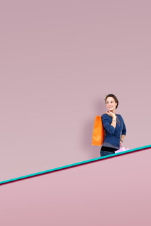 Smiling woman with shopping bags on an escalator in front of a pink wall - KLRF000261