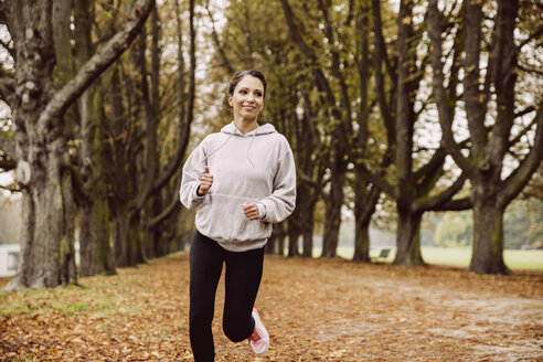 Woman jogging in park during autumn - MFF002453