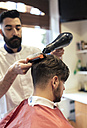 Barber blow-drying and brushing hair of a customer - MGOF000924
