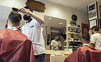 Two barbers cutting hair of twin brothers in barber shop - MGOF000927