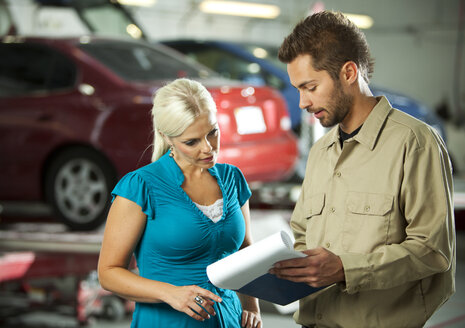 Man and customer in repair garage discussing ckeck list - SELF000074