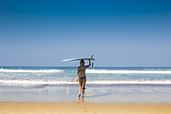 Indonesia, Bali, back view of woman carrying her surfboard on her head on the beach - KNTF000138