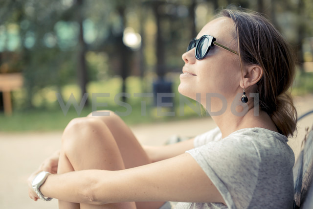 Woman wearing sunglasses relaxing in a park - KNTF000147