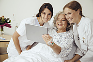 Senior woman in hospital showing doctor and nurse something on digital tablet - MFF002467