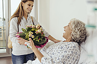 Granddaughter visiting grandmother in hospital, bringing bunch of flowers - MFF002476