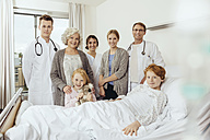 Doctors and famiy in hospital standing by bed of sick boy - MFF002497