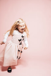 Laughing little girl running in front of pink background - IPF000261