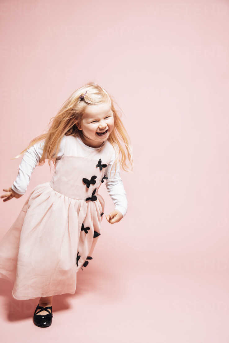 Laughing little girl running in front of pink background - IPF000261 - Ina Peters/Westend61