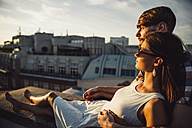 Austria, Vienna, Young couple enjoying romantic sunset on rooftop terrace - AIF000121